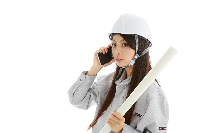 現場確認する作業着姿の若い女性