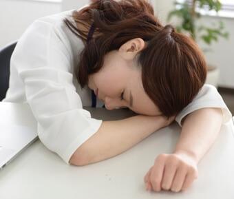 机に突っ伏して寝るキャリアウーマン