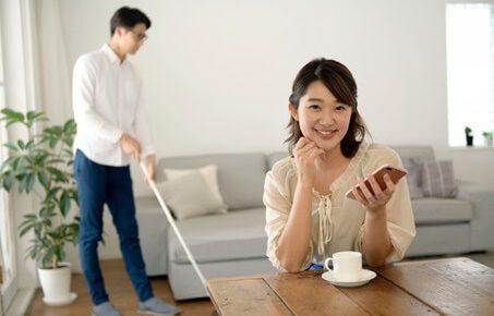 掃除する夫とスマホをみる妻
